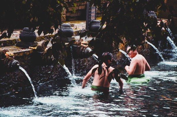 Männer baden im Pool vom Wassertempel Pura Tirta Empul bei Ubud