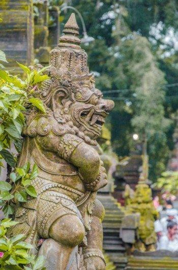 Wassertempel Pura Tirta Empul bei Ubud -Detail von Statue mit Grünzeug bewachsen