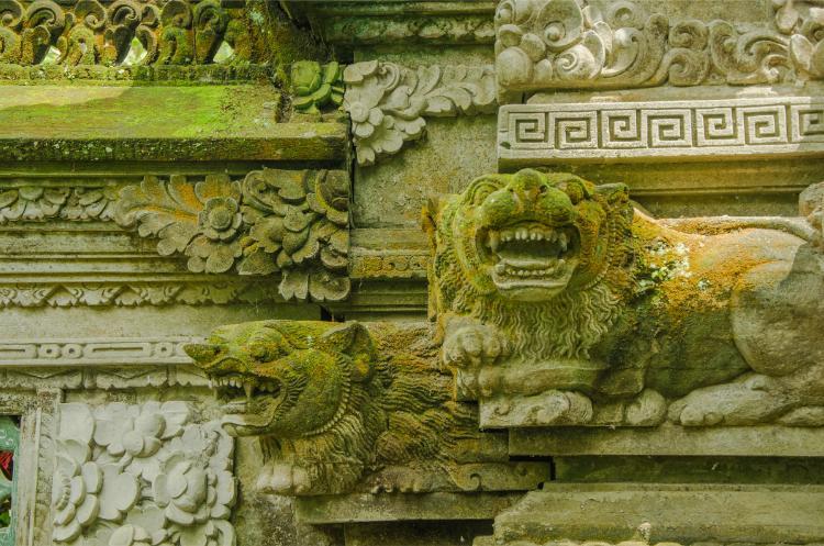 Detail mit bemoosten Löwen eines Tempels bei Ubud