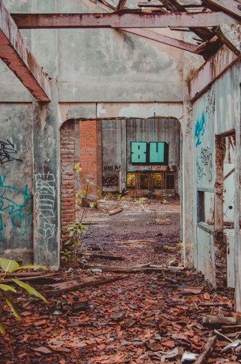 Ehemalige Räume mit Graffiti besprüht und Holzbalken am Boden, Taman Festival, Sanur
