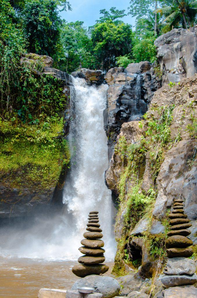 Tegenungan Wasserfall mit Steintürmen im Vordergrund