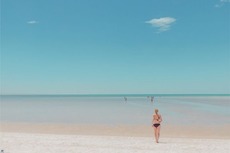 Strand in Westaustralien mit klaren Himmel und Frau in Bikini