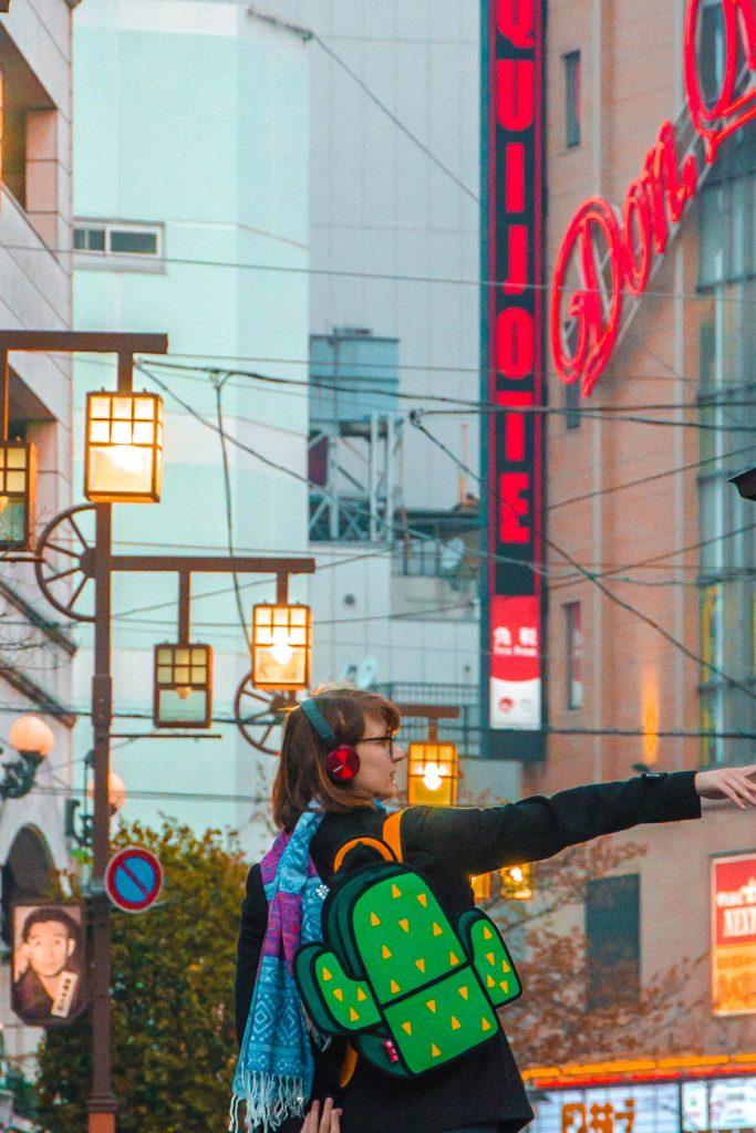 Bunter Rucksack in Kaktusform an Frau in einer erleuchteten Straße in Asakusa, Tokio