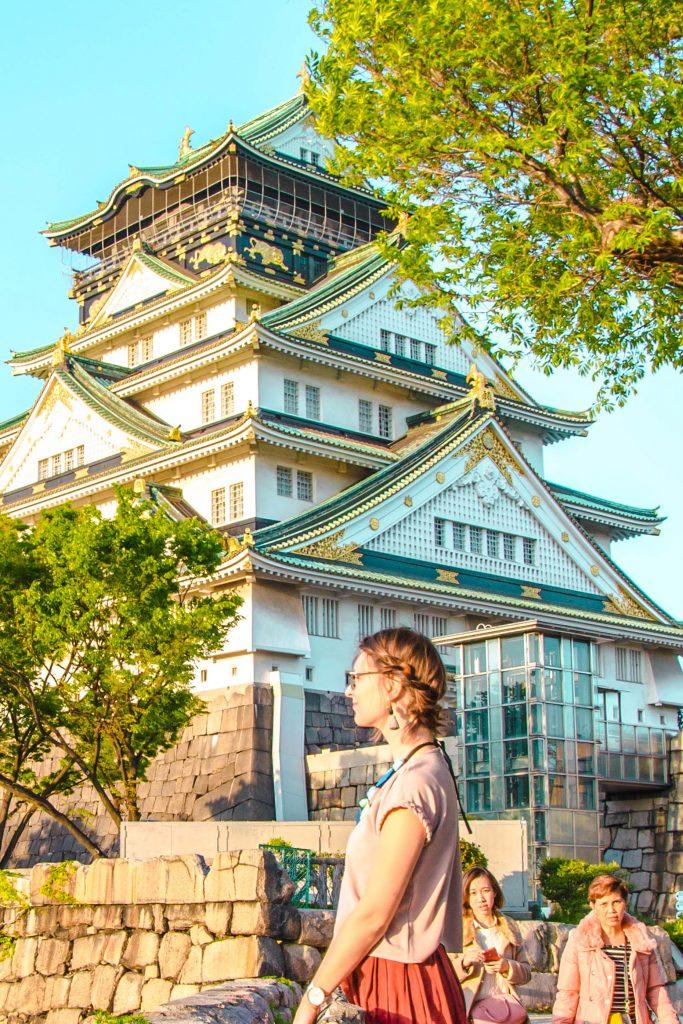 Frau in rosa Farben vor der weißen Osaka Burg, Japan