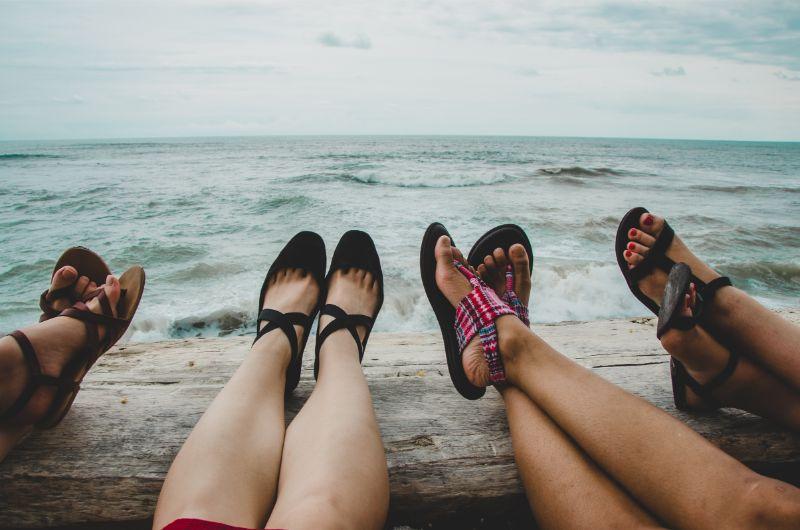 4 Mädels legen ihre Füße auf einer hölzernen Reeling ab, Blick aufs Meer