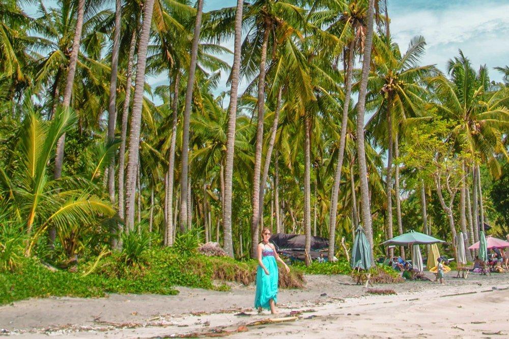 Frau im blauen Boho Kleid auf Nusa Penida am Strand unter Palmen