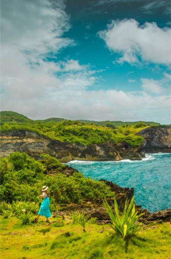 Frau in blauem Kleid am Broken Beach, Nusa Penida