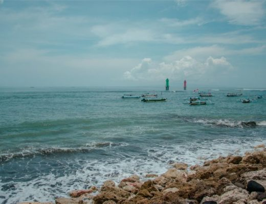 Sanur Strand auf Bali bei bewölktem Himmel mit Booten in der Ferne