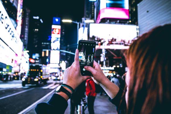 Frau fotografiert den Times Square bei Nacht mit dem Handy