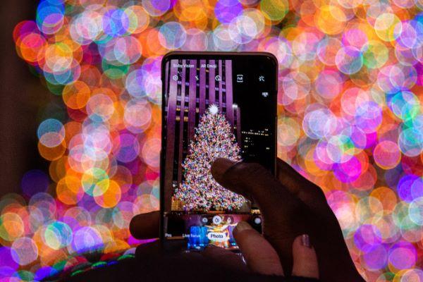 Handy vor bunterm Weihnachtsbaum am Rockefeller Center, NYC