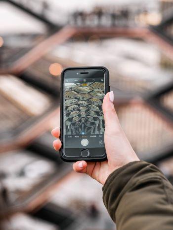 Frau fotografiert die Hudson Yards von oben mit Handy