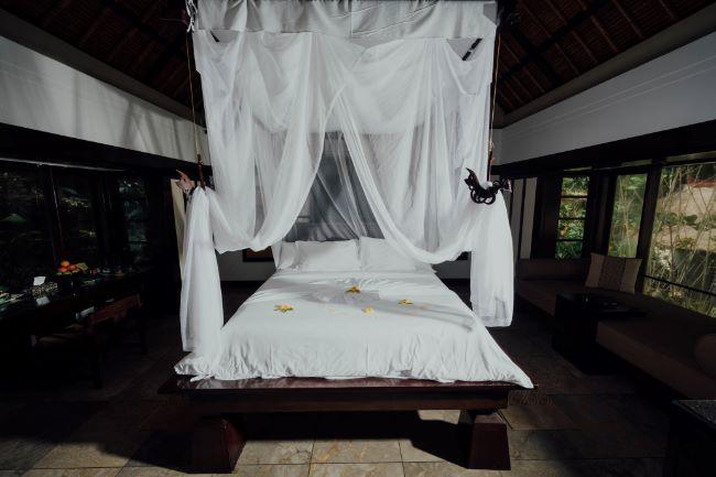 Mückenschutz im Urlaub durch Moskitonetz am Bett im Hotel