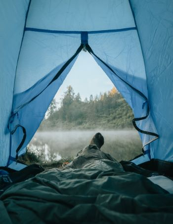 offenes Zelt mit Blick auf vernebelten See
