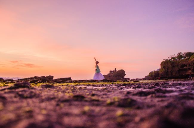 Frau tanzt bei Sonnenuntergang vor Tanah Lot Tempel in Bali