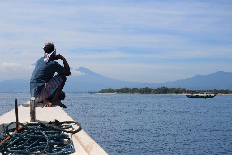 Mann auf Boot vor den Gili Inseln bei Bali, Indonesien