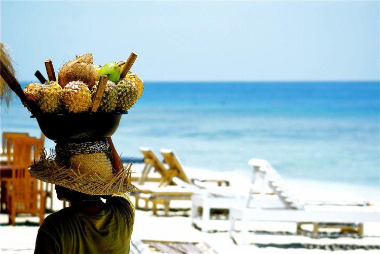 Frau mit Obstschale am Strand auf den Gili Inseln vor Bali