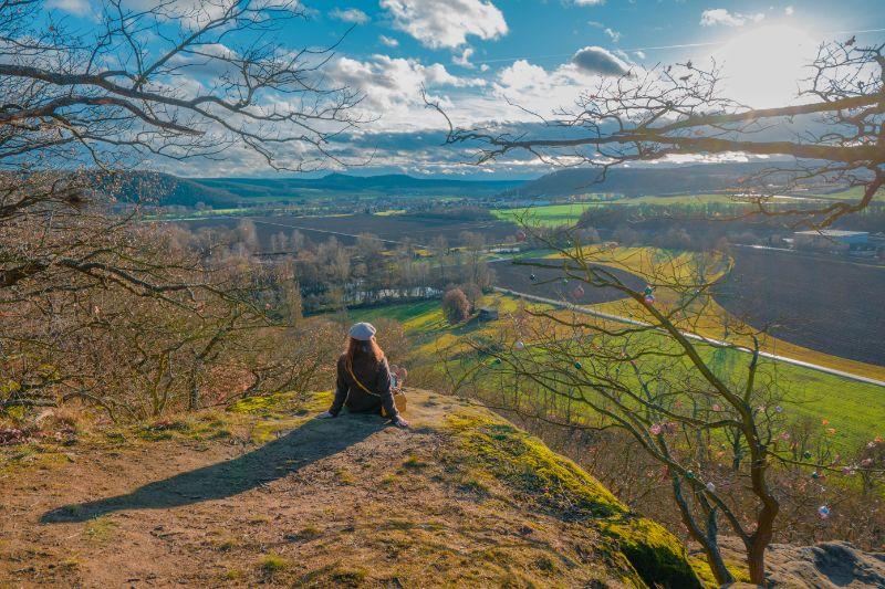 sitzende Frau auf Felsvorsprung mit Blick über weite Felder und blauem Himmel