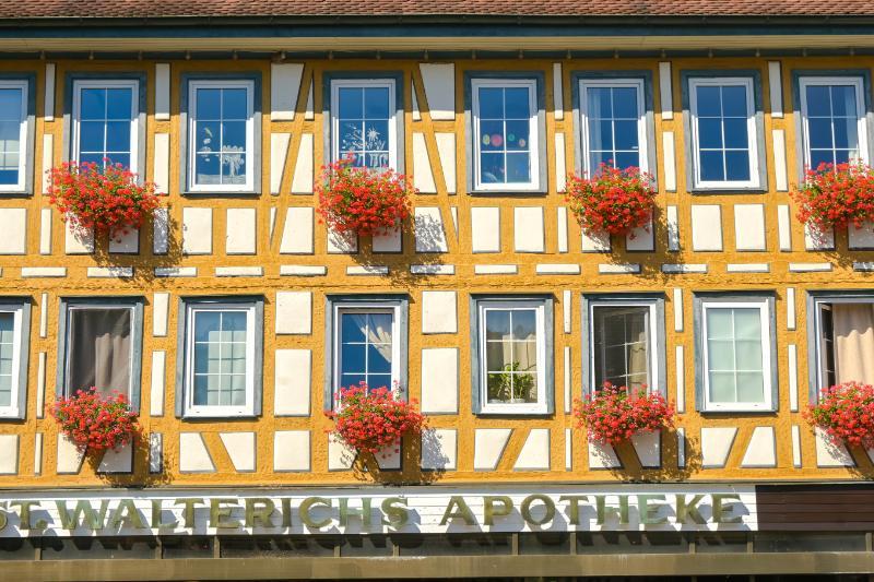 Walterichsapotheke mit gelbem Fachwerk und roten Blumen am Fenster