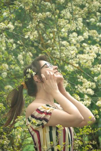 Frau vor Kirschblütenbaum