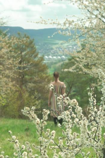 Frau inmitten von blühenden Kirschblüten auf Hügel