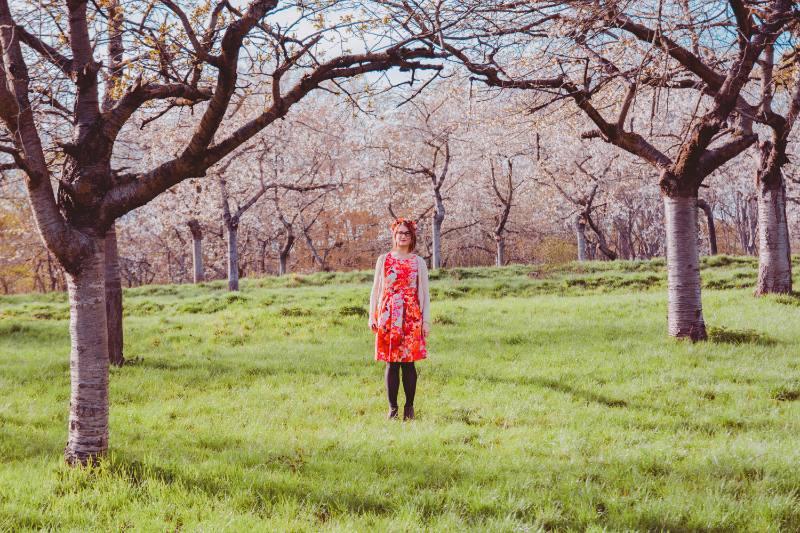 Frau inmitten blühender Kirschbäume
