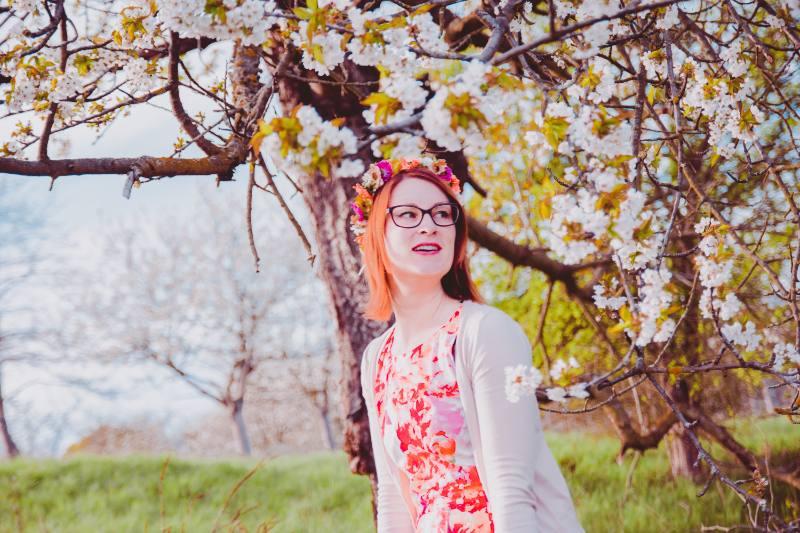 Frau in BLütenkleid vor weißen Kirschblüten