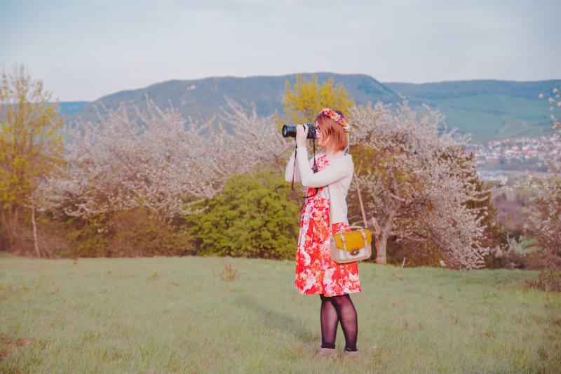Frau in Blumenkleid schießt Foto vor Kirschbäumen