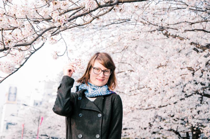 Frau in schwarzem Mantel vor riesigen blühenden Kirschbäumen