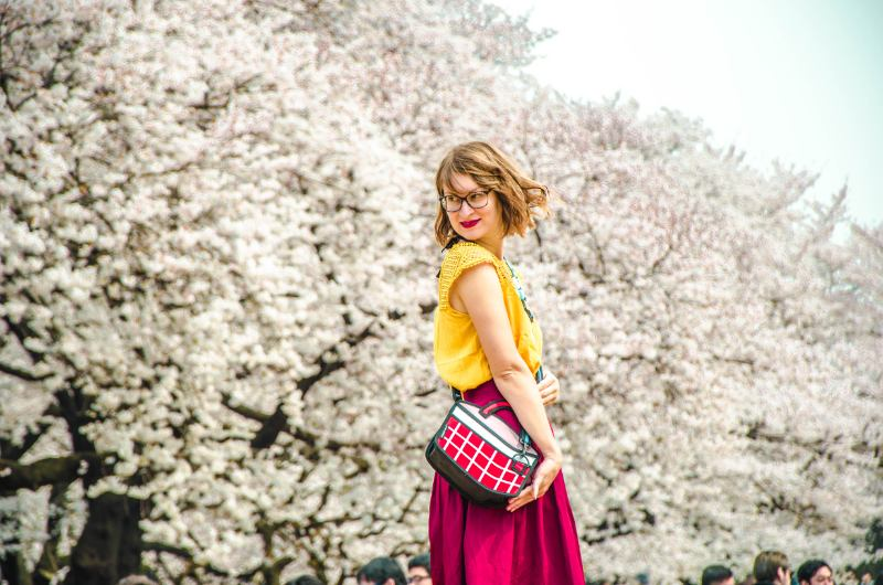 Frau in rot und gelb vor riesigen blühenden Kirschbäumen