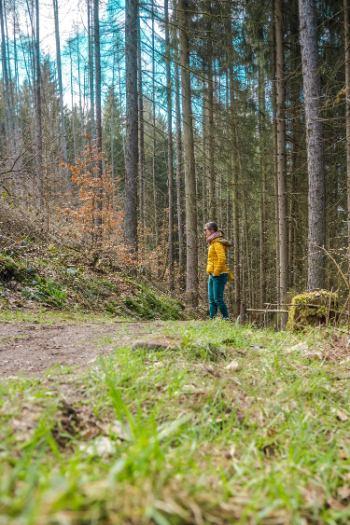 Frau in gelb auf einem Waldpfad im Grünen