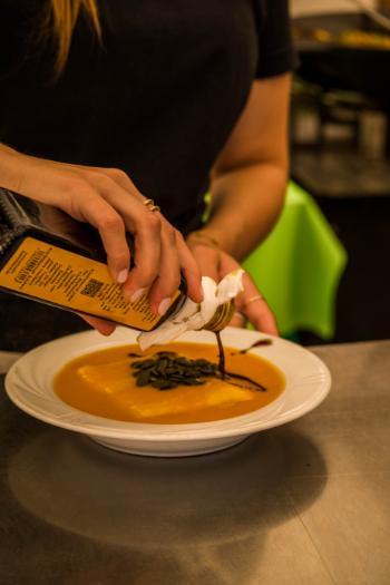 Balsamico wird auf Kürbissuppe gegossen