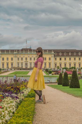 Frau in gelbem Rock posiert vor dem Residenzschloss Ludwigsburg umringt von blühenden Blumenbeeten